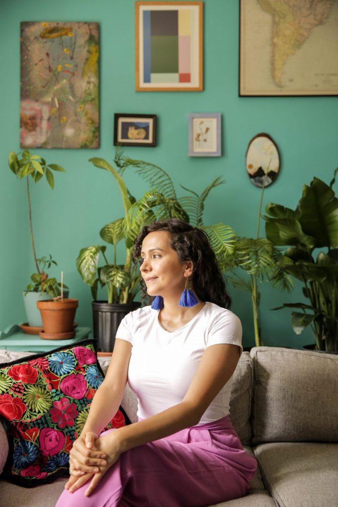 Diana Castro Sitting Cross Legged and Smiling  Photo by Itzel Alejandra Martinez for Remezcla
